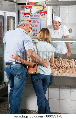 Loving mature couple standing in butcher's shop