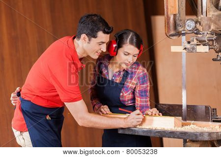 Young male and female carpenters measuring wood in workshop