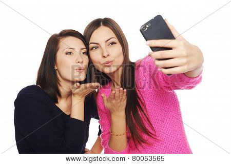 Two girls friends taking selfie with smartphone