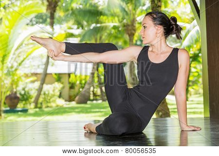Young Woman Is Practicing Yoga And Pilates On Nature. Morning Meditation At Summer