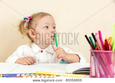 Cute Child Girl Drawing With Colorful Pencils And Felt-tip Pen In Preschool At Table In Kindergarten