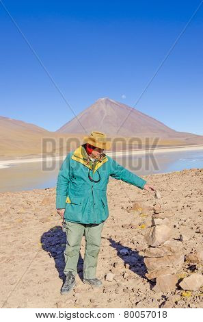 Bolivia, Antiplano - senior tourist watches cairn (Quechuan shrine ).  Laguna Verde and Licancabur volcano in background, Eduardo Avaroa Andean Fauna National Reserve, Sur Lipez, Bolivia
