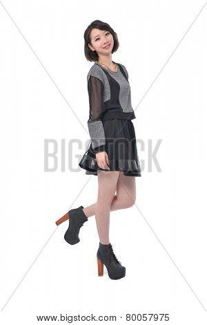 Full body model wearing fashionable clothing walking in studio