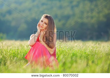 Portrait of beautiful young woman in red dress sitting in the grass in summer