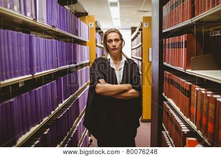 Unsmiling lawyer standing between shelfs with arms crossed in library