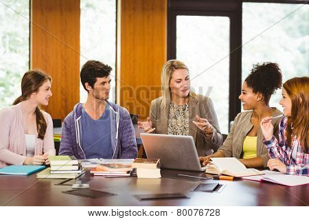 Smiling female with students and teacher in library at the university