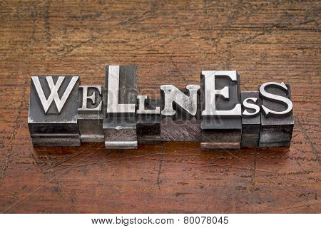 wellness word in mixed vintage metal type printing blocks over grunge wood