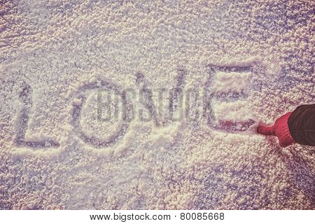 Written Or Drawn By Hand In Pink Glove Word Love On White Snow