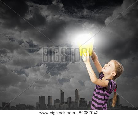 Cute girl with bucket and light bulb in it