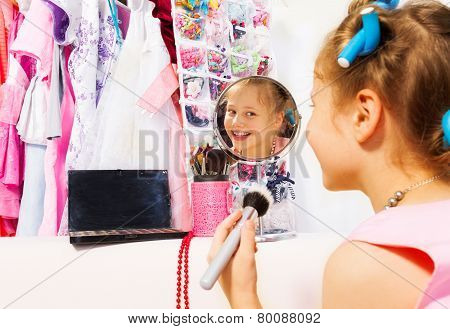 Happy girl makes up with brush looking in mirror