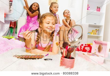 Girl makeup with brush and her friends behind