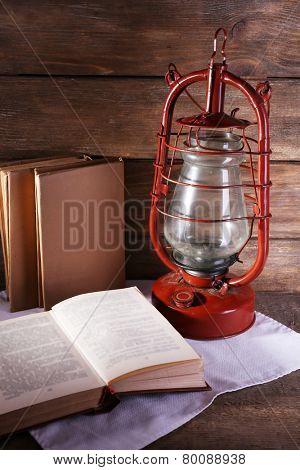 Kerosene lamp with books on rustic wooden background