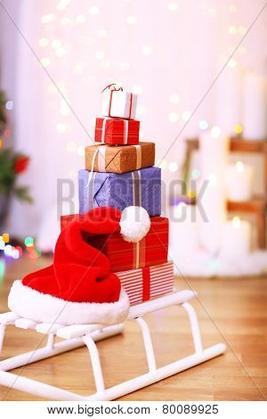 Present boxes on sledge on wooden floor near Christmas tree, indoors