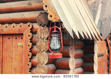 Kerosene lamp hanging on wooden house, outdoors