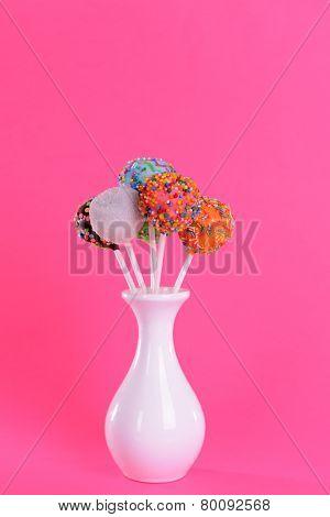 Sweet cake pops in vase on pink background