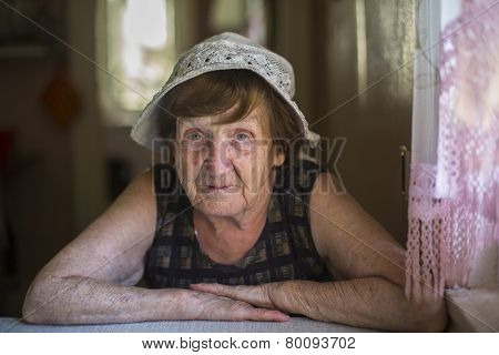 Old woman in the kitchen of his farmhouse.