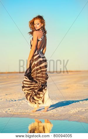 Beautiful young woman dancing outdoors near a lake