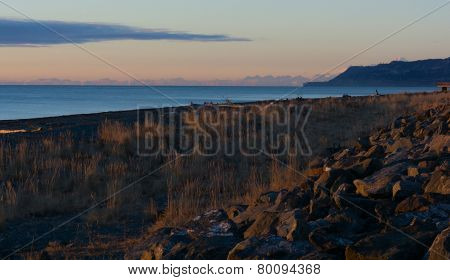 Rocky Breakwater With Alaskan Range In Background