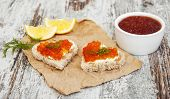 stock photo of canapes  - canape with red caviar on a old wooden background - JPG