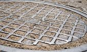 image of manhole  - Metal manhole cover with checkered surface - JPG