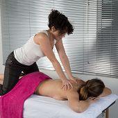 stock photo of thai massage  - Woman lying on mat receiving massage from thai therapist  - JPG
