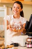 stock photo of cashiers  - Beautiful young female cashier in apron standing near cash register and stretching out cookies.