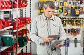 picture of hardware  - Mature male customer analyzing product through digital tablet in hardware store - JPG