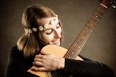 stock photo of ordinary woman  - Young woman with acoustic guitar and flower hairband - JPG