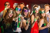 image of masquerade mask  - Friends in masquerade masks drinking champagne at the nightclub - JPG