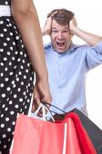 stock photo of reaction  - Caucasian man with expression and reaction of shock upon seeing wife with hands full of shopping bags on white background - JPG