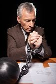 foto of white collar crime  - Frustrated senior man in formalwear sitting at his working place and looking at camera while isolated on black background - JPG