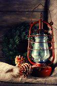 picture of kerosene lamp  - Kerosene lamp with wreath and cones on wooden planks background - JPG