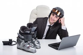 picture of ski boots  - Young businessman in the office is wearing a helmet and ski boots on the table - JPG