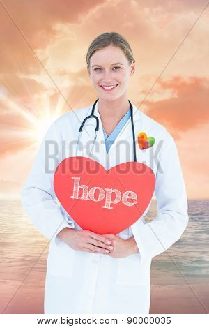 The word hope and doctor holding red heart card against sunrise over magical sea