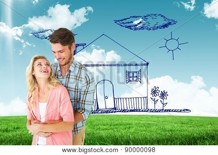 Attractive young couple embracing and smiling against blue sky over green field