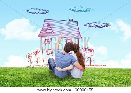 Couple sitting on floor together against blue sky over green field