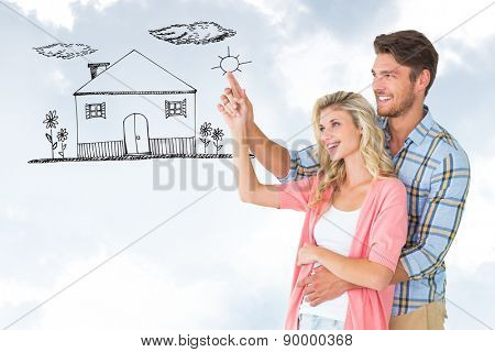 Attractive young couple embracing and pointing against blue sky