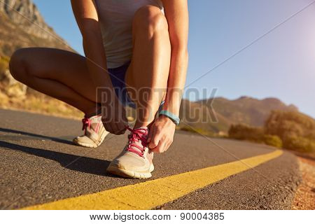 Cropped shot of female jogger doing up her shoe lace