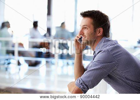 Portrait of man talking on phone, office interior