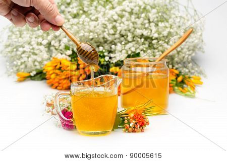 Honey pours in a jar from a stick hold by hand. Flowers are near and in background