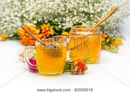 Two Honey jars with stick and flowers near. Isolated on pure white