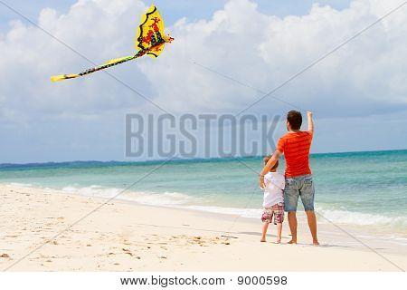 Padre e hijo volar la cometa en la playa