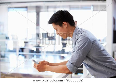 Portrait of young man using smart phone in an office
