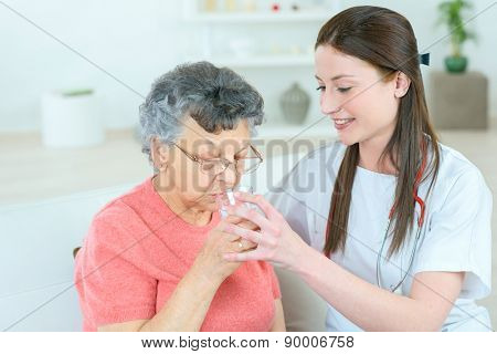 Giving senior lady a glass of water