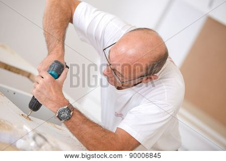 Carpenter using an electric screwdriver