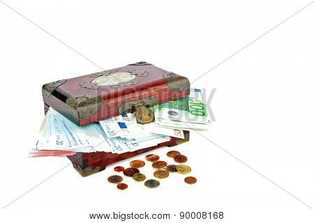 Old wooden chest with euro banknotes and coins