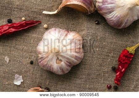 Garlic heads and red chili peppers on hessian fabric cloth background