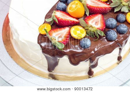 Cake with strawberries, blueberries, kumquat drizzled with chocolate
