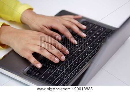business, technology, school, people and education concept - close up of african american businesswoman or student girl hands with laptop computer sitting at table