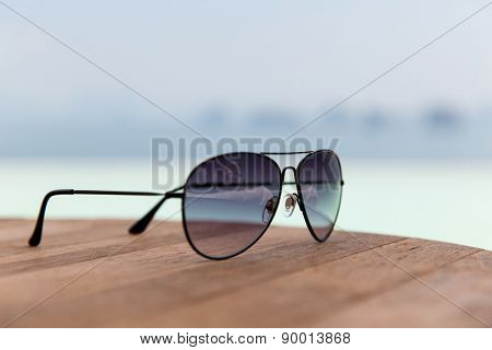 travel, tourism, summer vacation and fashon accessories concept - shades or sunglasses on table at beach